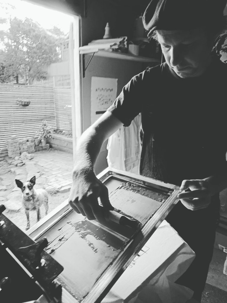 Person screen printing with dog in background