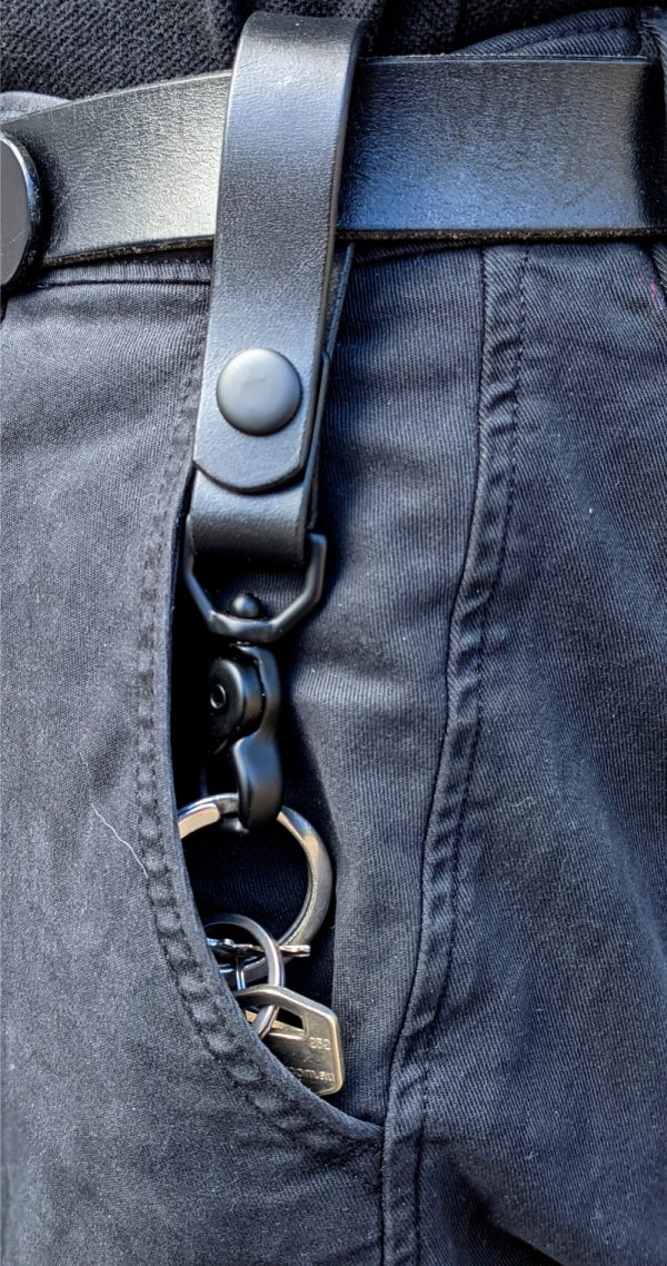 Leather belt hanger with key attached and sitting in trouser pocket